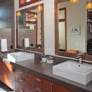 Idée de décoration pour une grand salle de bain principale craftsman avec un placard à porte plane, des portes de placard en bois brun, une baignoire encastrée, une douche d'angle, un WC séparé, un carrelage marron, des carreaux de porcelaine, un mur beige, un sol en ardoise, une vasque, un plan de toilette en surface solide, un sol gris et une cabine de douche à porte battante.