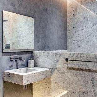 Ejemplo de cuarto de baño contemporáneo con lavabo suspendido, baldosas y/o azulejos grises, losas de piedra, paredes grises y suelo de madera oscura