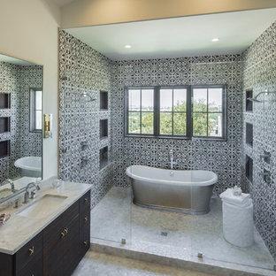 Salle de bain avec un carrelage noir et blanc et un sol en galet ...