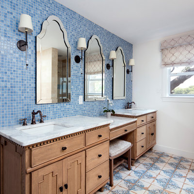 Example of a beach style blue tile and mosaic tile multicolored floor bathroom design in Austin with furniture-like cabinets, medium tone wood cabinets, white walls, an undermount sink and white countertops