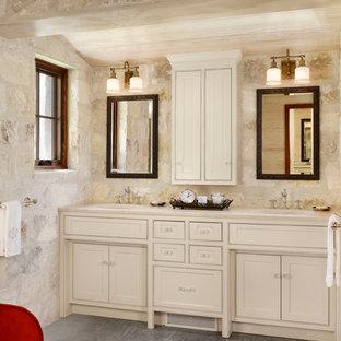 Modelo de cuarto de baño de estilo de casa de campo con lavabo bajoencimera, armarios con rebordes decorativos, puertas de armario beige y baldosas y/o azulejos de piedra