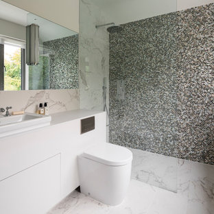 Photo of a large contemporary bathroom in London with flat-panel cabinets, beige cabinets, a corner shower, a one-piece toilet, mosaic tiles, marble flooring, a vessel sink, white floors, an open shower and white worktops.