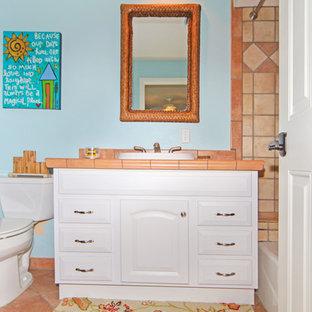 Modelo de cuarto de baño con ducha, costero, con armarios con paneles con relieve, puertas de armario blancas, bañera encastrada, ducha abierta, sanitario de dos piezas, baldosas y/o azulejos naranja, baldosas y/o azulejos de cerámica, paredes azules, suelo de baldosas de cerámica, lavabo bajoencimera, encimera de azulejos, suelo naranja y ducha con cortina