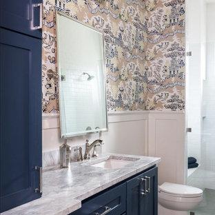 Cette image montre une salle de bain traditionnelle avec un placard à porte shaker, des portes de placard bleues, un mur multicolore, un lavabo encastré, un sol gris, une cabine de douche à porte battante et un plan de toilette blanc.
