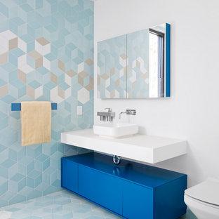 На фото: ванная комната в современном стиле с плоскими фасадами, синими фасадами, синей плиткой, настольной раковиной, синим полом, белой столешницей, тумбой под одну раковину и подвесной тумбой с