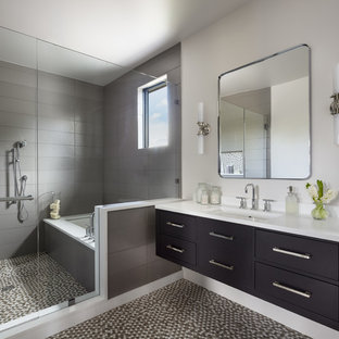 Inspiration for a large eclectic master gray tile and subway tile mosaic tile floor and multicolored floor bathroom remodel in Denver with flat-panel cabinets, black cabinets, white walls, a drop-in sink, solid surface countertops, a hinged shower door and white countertops