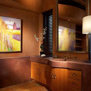 Imagen de cuarto de baño minimalista, grande, con lavabo integrado, armarios con paneles lisos, puertas de armario de madera oscura, suelo de baldosas de terracota, encimera de cemento y paredes rosas
