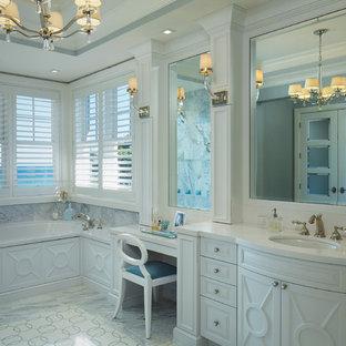 Modelo de cuarto de baño con ducha, costero, grande, con armarios con paneles con relieve, puertas de armario blancas, bañera empotrada, ducha a ras de suelo, baldosas y/o azulejos azules, baldosas y/o azulejos grises, baldosas y/o azulejos de mármol, paredes azules, suelo de mármol, lavabo bajoencimera, encimera de cuarzo compacto, suelo gris, ducha con puerta con bisagras y encimeras blancas