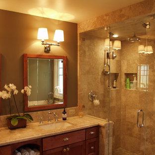 サンフランシスコの中くらいのトラディショナルスタイルのおしゃれな浴室 (アンダーカウンター洗面器、シェーカースタイル扉のキャビネット、中間色木目調キャビネット、大理石の洗面台、ドロップイン型浴槽、コーナー設置型シャワー、一体型トイレ、ベージュのタイル、石タイル、茶色い壁、セラミックタイルの床) の写真