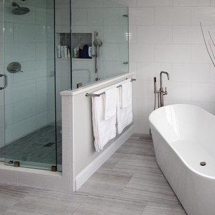 フィラデルフィアの大きいコンテンポラリースタイルのおしゃれなマスターバスルーム (シェーカースタイル扉のキャビネット、グレーのキャビネット、置き型浴槽、コーナー設置型シャワー、一体型トイレ、白いタイル、磁器タイル、グレーの壁、磁器タイルの床、アンダーカウンター洗面器、珪岩の洗面台、ベージュの床、開き戸のシャワー) の写真