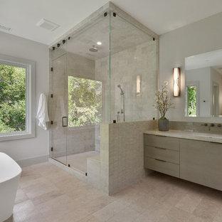 Inspiration för moderna beige en-suite badrum, med släta luckor, skåp i ljust trä, ett fristående badkar, en hörndusch, beige kakel, grå väggar, ett undermonterad handfat, beiget golv och dusch med gångjärnsdörr