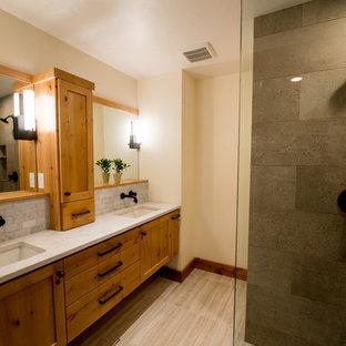 Imagen de cuarto de baño principal, de estilo americano, de tamaño medio, con armarios estilo shaker, puertas de armario de madera oscura, ducha abierta, sanitario de pared, baldosas y/o azulejos grises, baldosas y/o azulejos de mármol, paredes beige, suelo de baldosas de porcelana, lavabo de seno grande, encimera de cuarcita, suelo beige y ducha abierta