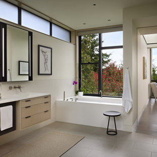 Inspiration for a modern bathroom remodel in Seattle with flat-panel cabinets, light wood cabinets and an undermount tub