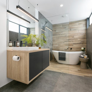 Photo of a contemporary master bathroom in Hobart with flat-panel cabinets, green cabinets, a freestanding tub, a curbless shower, a wall-mount toilet, gray tile, white walls, a vessel sink, wood benchtops, grey floor and an open shower.