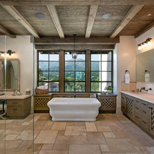 Example of a tuscan beige tile brown floor freestanding bathtub design in Santa Barbara with flat-panel cabinets, medium tone wood cabinets, white walls, an undermount sink and beige countertops