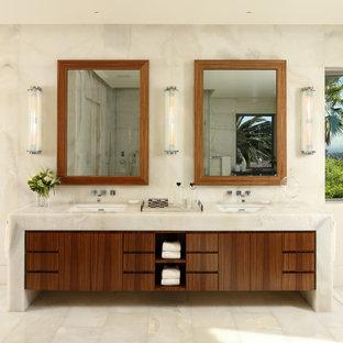 Ejemplo de cuarto de baño actual con lavabo bajoencimera, armarios con paneles lisos, puertas de armario de madera en tonos medios, encimera de ónix, paredes beige y baldosas y/o azulejos beige