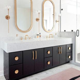 Cette photo montre une salle de bain principale rétro avec un placard à porte plane, des portes de placard noires, un mur blanc, un lavabo encastré et un plan de toilette blanc.