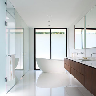 Example of a minimalist master white floor bathroom design in New York with an undermount sink, flat-panel cabinets, dark wood cabinets and white walls