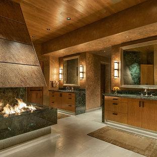 Esempio di un'ampia stanza da bagno padronale stile americano con ante lisce, ante in legno scuro, pareti marroni, vasca da incasso, doccia ad angolo, piastrelle beige, piastrelle in pietra, pavimento in marmo, lavabo sottopiano e top in granito