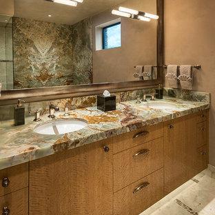 На фото: большая главная ванная комната в современном стиле с плоскими фасадами, светлыми деревянными фасадами, раздельным унитазом, бежевой плиткой, каменной плиткой, бежевыми стенами, мраморным полом, врезной раковиной и столешницей из оникса с