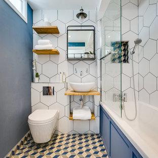 Foto di una piccola stanza da bagno con doccia design con vasca da incasso, vasca/doccia, WC sospeso, piastrelle bianche, pareti blu, lavabo a bacinella, top in legno, pavimento multicolore, doccia aperta e top marrone