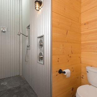 Modelo de cuarto de baño principal, rústico, de tamaño medio, con armarios abiertos, puertas de armario de madera clara, ducha abierta, sanitario de dos piezas, baldosas y/o azulejos de metal, suelo de cemento, lavabo sobreencimera, encimera de madera, suelo negro y ducha abierta