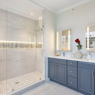 ボストンの中くらいのトランジショナルスタイルのおしゃれなマスターバスルーム (レイズドパネル扉のキャビネット、グレーのキャビネット、アルコーブ型シャワー、グレーのタイル、磁器タイル、グレーの壁、磁器タイルの床、アンダーカウンター洗面器、クオーツストーンの洗面台、グレーの床、オープンシャワー、白い洗面カウンター) の写真