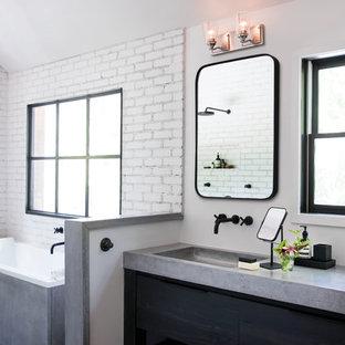 Diseño de cuarto de baño con ducha, urbano, sin sin inodoro, con armarios con paneles lisos, puertas de armario negras, bañera esquinera, baldosas y/o azulejos blancos, paredes blancas, suelo de madera en tonos medios, lavabo integrado, encimera de cemento, suelo marrón y ducha abierta
