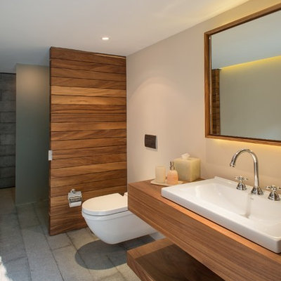 Inspiration for a mid-sized modern bathroom remodel in Mexico City with a vessel sink, a wall-mount toilet, wood countertops and brown countertops