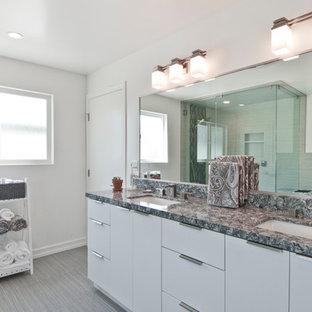Imagen de cuarto de baño principal, moderno, de tamaño medio, con armarios con paneles lisos, puertas de armario blancas, ducha esquinera, paredes grises, suelo vinílico, lavabo bajoencimera, encimera de granito, suelo gris, ducha con puerta con bisagras y encimeras grises