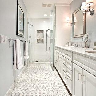 Aménagement d'une salle d'eau classique avec un placard avec porte à panneau encastré, des portes de placard blanches, une douche double, un carrelage blanc, des carreaux de céramique, un mur bleu, un sol en carrelage de terre cuite, un lavabo encastré et un plan de toilette en marbre.