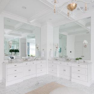 Cette image montre une très grand salle de bain principale traditionnelle avec un placard à porte shaker, des portes de placard blanches, un mur blanc, un sol en marbre, un lavabo encastré, un plan de toilette en marbre, un sol blanc, un plan de toilette blanc, meuble double vasque, meuble-lavabo encastré et un plafond à caissons.