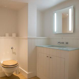Diseño de cuarto de baño infantil, clásico, de tamaño medio, con sanitario de una pieza, baldosas y/o azulejos blancos, paredes blancas, suelo de madera clara, lavabo encastrado, armarios estilo shaker, puertas de armario blancas, encimera de vidrio reciclado y encimeras turquesas