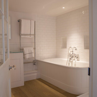 Photo of a medium sized classic family bathroom in Oxfordshire with a built-in bath, a shower/bath combination, a one-piece toilet, white tiles, stone tiles, white walls, light hardwood flooring, a built-in sink and an open shower.