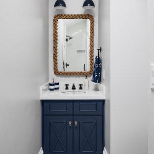 フェニックスの小さいビーチスタイルのおしゃれな子供用バスルーム (青いキャビネット、グレーの壁、アンダーカウンター洗面器、珪岩の洗面台、白い洗面カウンター、家具調キャビネット、モザイクタイル、グレーの床) の写真