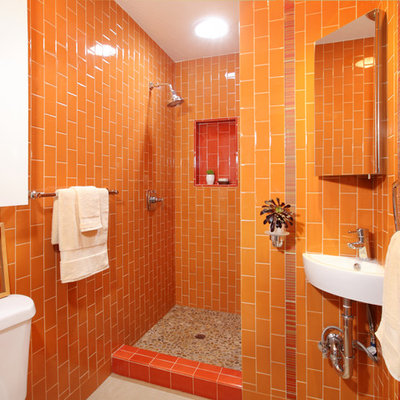 Eclectic orange tile pebble tile floor bathroom photo in Los Angeles with a wall-mount sink and orange walls