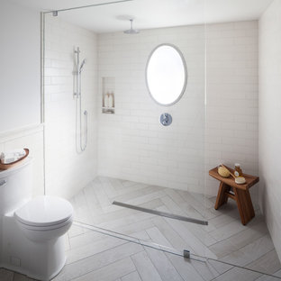 Imagen de cuarto de baño con ducha, contemporáneo, de tamaño medio, con armarios con paneles lisos, puertas de armario grises, ducha a ras de suelo, sanitario de una pieza, baldosas y/o azulejos blancos, baldosas y/o azulejos de cerámica, paredes grises, suelo de baldosas de cerámica, lavabo bajoencimera, encimera de ónix, suelo gris y ducha abierta