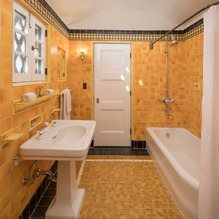 Design ideas for a small mediterranean ensuite bathroom in Los Angeles with a corner bath, a shower/bath combination, yellow tiles, ceramic tiles, yellow walls, ceramic flooring, a pedestal sink and a shower curtain.