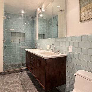 Ispirazione per una piccola stanza da bagno padronale design con ante lisce, ante in legno bruno, doccia alcova, WC monopezzo, piastrelle blu, piastrelle di vetro, pareti bianche, pavimento in ardesia, lavabo sottopiano e top in superficie solida