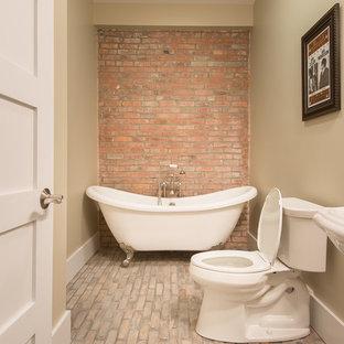 Esempio di una stanza da bagno con doccia tradizionale di medie dimensioni con lavabo a colonna, vasca con piedi a zampa di leone, WC a due pezzi, pareti beige e pavimento in mattoni