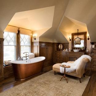 Inspiration for a mediterranean bathroom in Santa Barbara with recessed-panel cabinets, dark wood cabinets, a freestanding bath, beige walls, dark hardwood flooring, a vessel sink and brown floors.