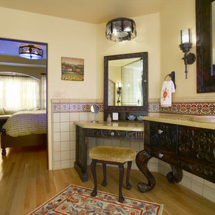 Example of a tuscan multicolored tile and ceramic tile light wood floor drop-in bathtub design in San Diego with a drop-in sink, dark wood cabinets, granite countertops and yellow walls