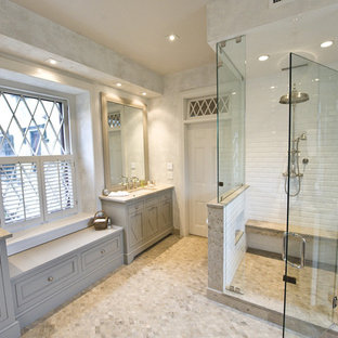 Expansive traditional master bathroom in Philadelphia with subway tile, limestone floors, limestone benchtops, multi-coloured floor and a hinged shower door.