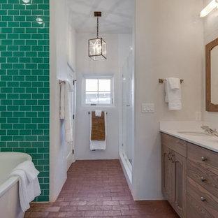 アルバカーキの中くらいのサンタフェスタイルのおしゃれなマスターバスルーム (アンダーカウンター洗面器、落し込みパネル扉のキャビネット、中間色木目調キャビネット、人工大理石カウンター、シャワー付き浴槽、白いタイル、白い壁、レンガの床) の写真
