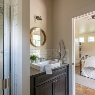 Small classic shower room bathroom in Other with shaker cabinets, dark wood cabinets, an alcove shower, white tiles, metro tiles, beige walls, medium hardwood flooring, a vessel sink, laminate worktops, brown floors, a hinged door and beige worktops.