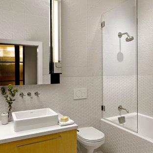 Aménagement d'une salle de bain industrielle de taille moyenne avec une vasque, un placard à porte plane, une baignoire en alcôve, un combiné douche/baignoire, un WC suspendu, un carrelage blanc, un mur blanc et des portes de placard jaunes.