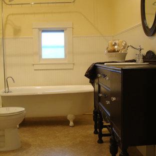 Ispirazione per una stanza da bagno padronale tradizionale di medie dimensioni con ante in legno bruno, top in legno, vasca con piedi a zampa di leone, pareti beige e pavimento in linoleum