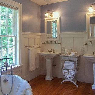 Mittelgroßes Klassisches Badezimmer En Suite mit Löwenfuß-Badewanne, lila Wandfarbe, braunem Holzboden, Sockelwaschbecken und braunem Boden in Raleigh