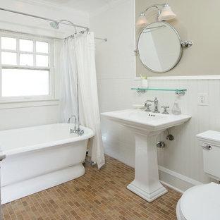 Пример оригинального дизайна: ванная комната в викторианском стиле с раковиной с пьедесталом, отдельно стоящей ванной, душем над ванной, белой плиткой, плиткой кабанчик и кирпичным полом