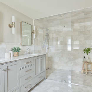 Example of a transitional master gray tile and marble tile marble floor, gray floor and double-sink walk-in shower design in Other with shaker cabinets, gray cabinets, gray walls, marble countertops, a hinged shower door, gray countertops, an undermount sink and a freestanding vanity